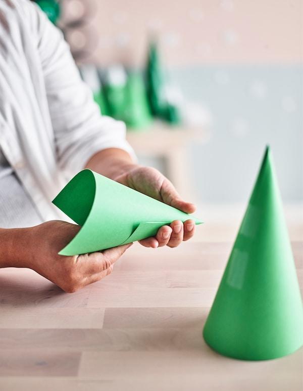 用手将纸卷成锥体,作为基督降临节日历树。