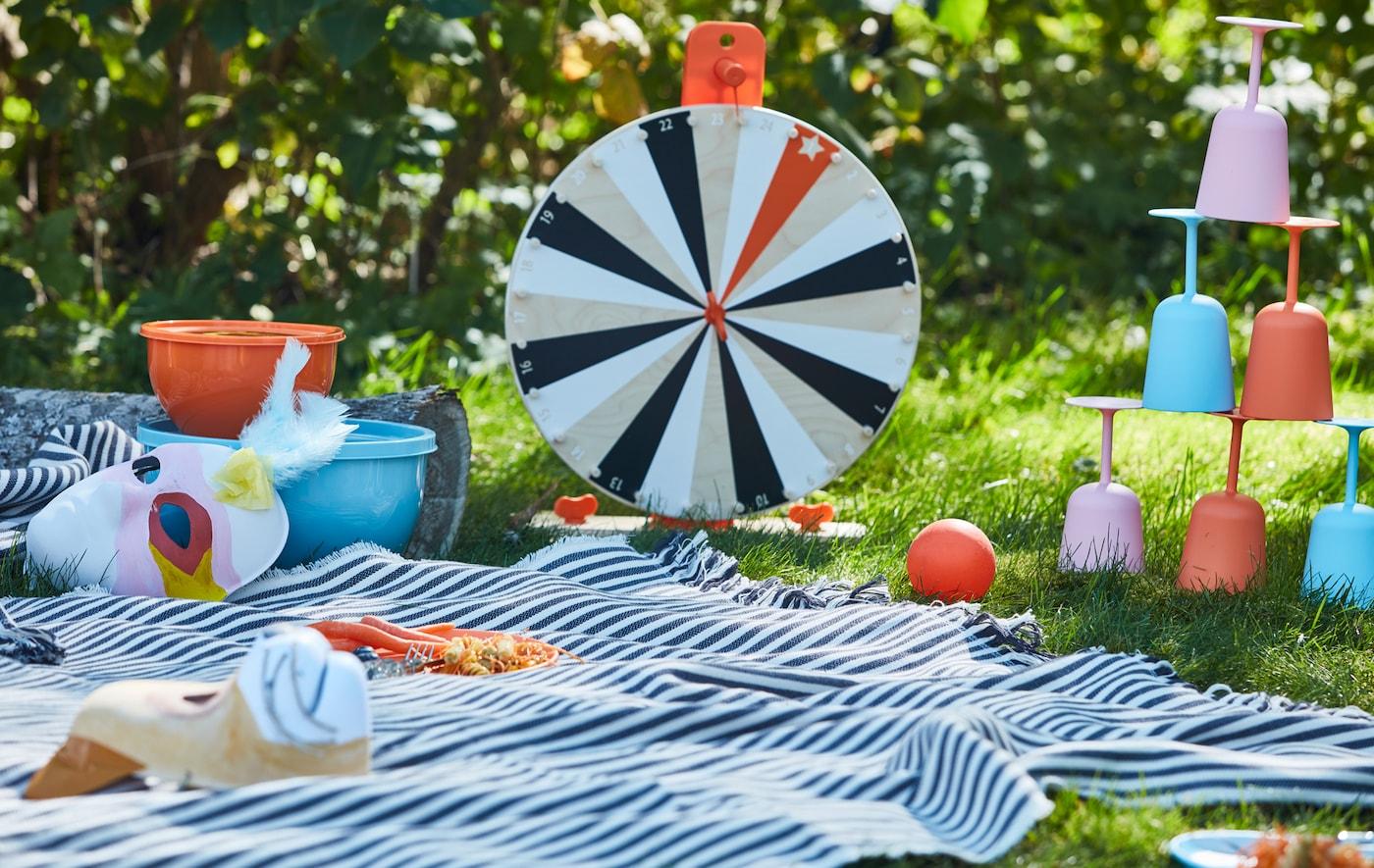 有很多游戏用品,其中有一个 LUSTIGT 卢斯蒂格 财富转盘游戏木转盘,野餐毯上摆放着不易碎的餐具。