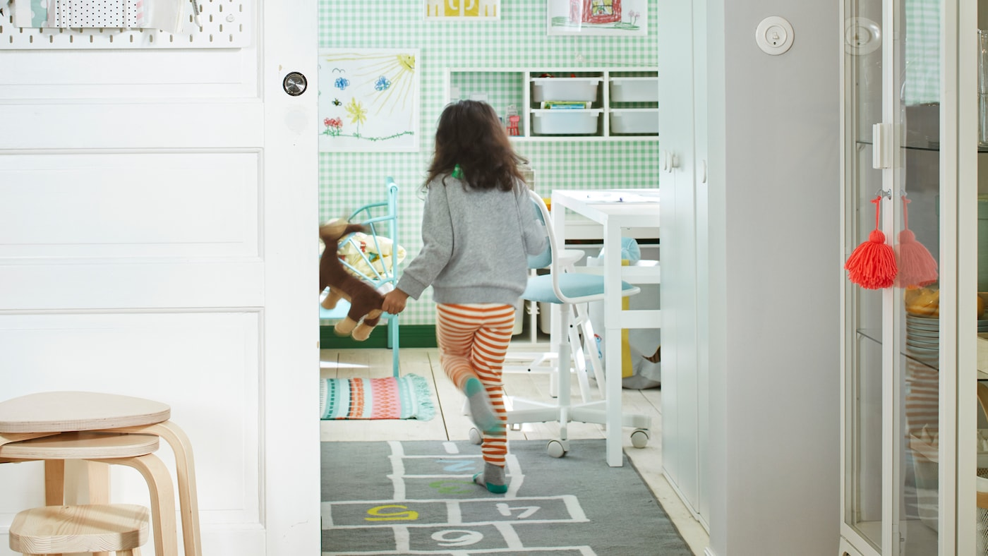 Young child running through the open, sliding door of a white-and-green room furnished with a bed, storage, a desk, and more.