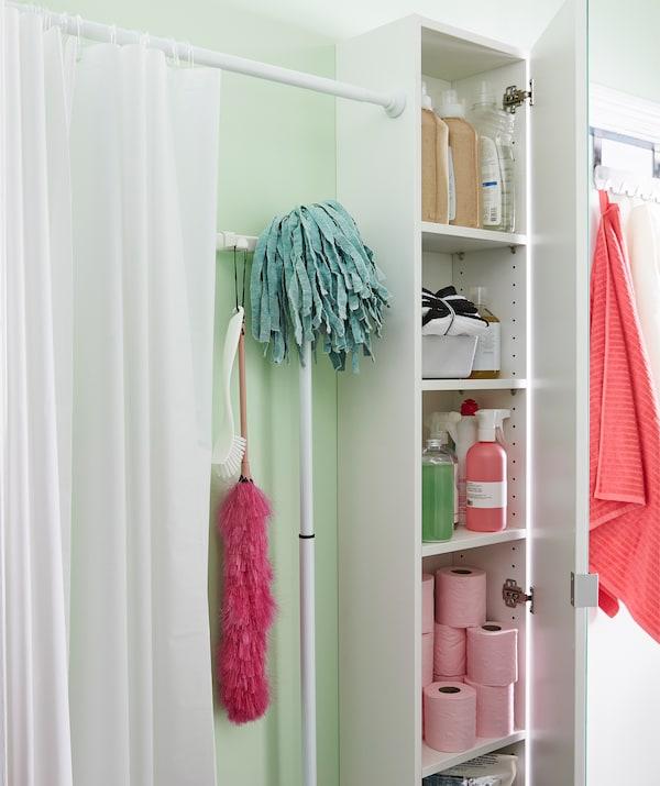 浴帘沿着浴室墙壁隔出一片小天地。一旁的橱柜里放着浴室配件。