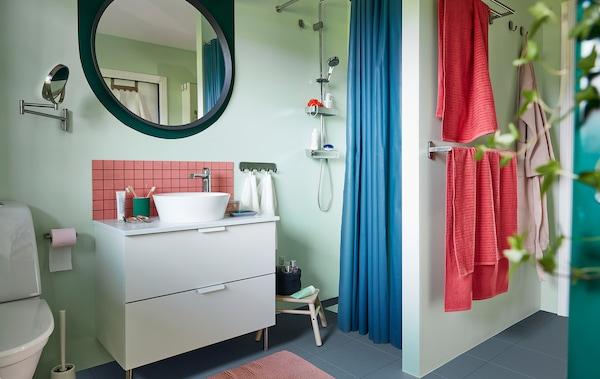 浴室井然有序,采用柔和的浅色调,配备洗脸池、淋浴花洒、毛巾杆、镜子、植物和配件。