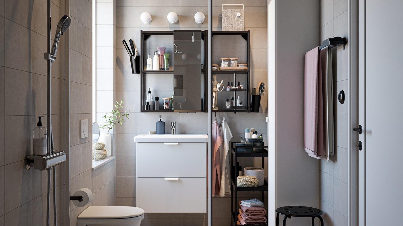 浴室里摆放着黑色/白色浴室家具,一个镀铬淋浴组合、浅粉色毛巾和玻璃淋浴门。