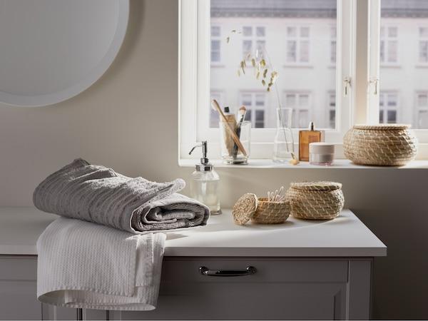 浴室里的 GODMORGON 古德莫 洗脸池柜上摆放着毛巾、储物件和皂液器,背后是一扇窗户,可欣赏宜人美景。