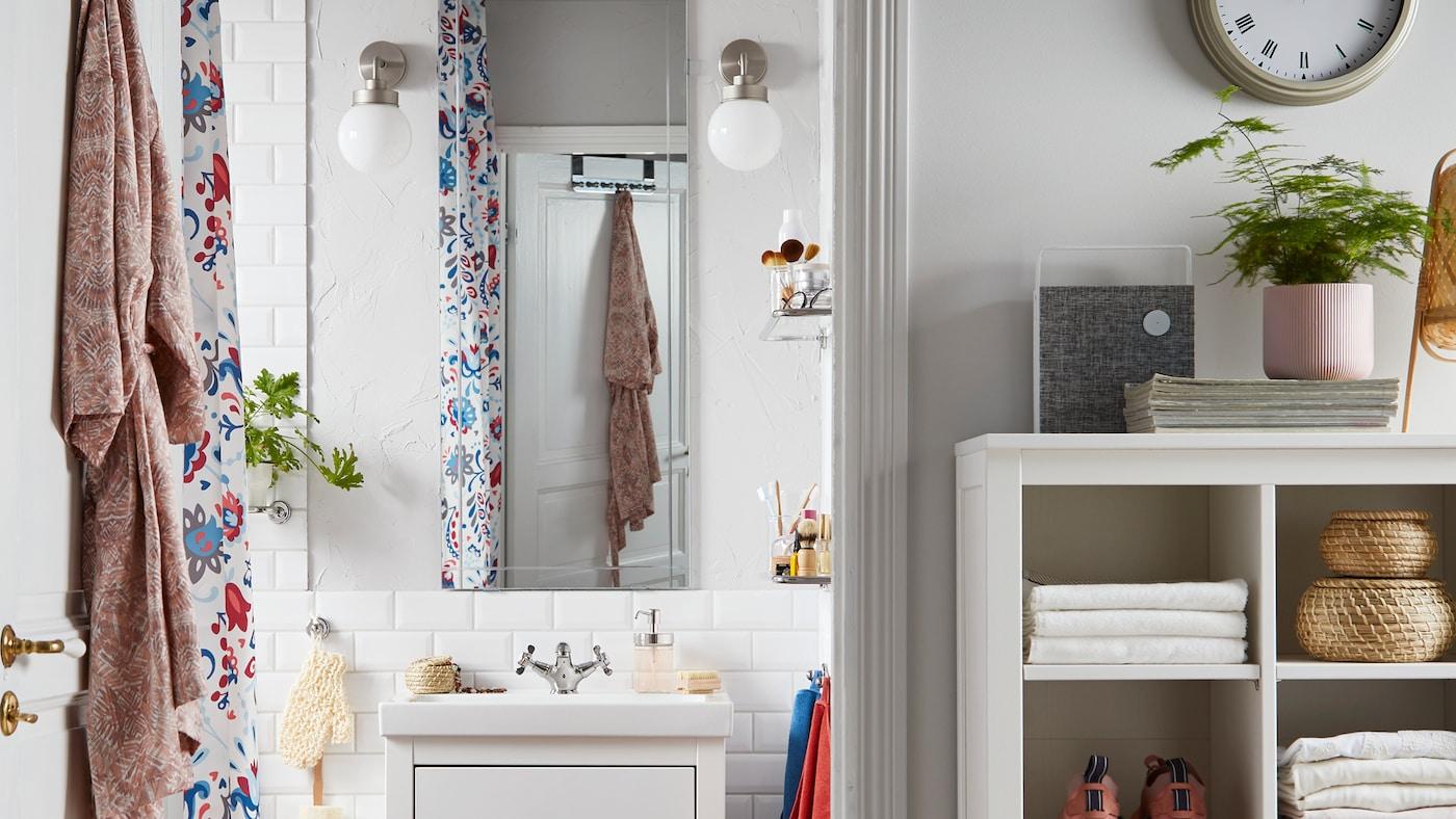浴室里有一面EIDSÅ 爱萨 镜子,两盏白色的FRIHULT 弗利荷 壁灯,一个放着毛巾、运动鞋和藤篮的储物单元。