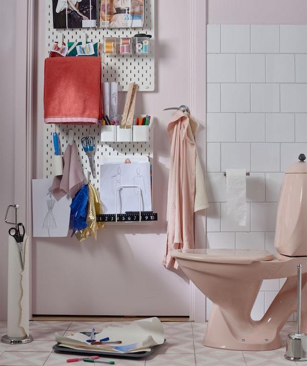 浴室内配件,门上配备钉板,用来放置笔、画纸等物品,纸和笔位于抽水马桶旁边。
