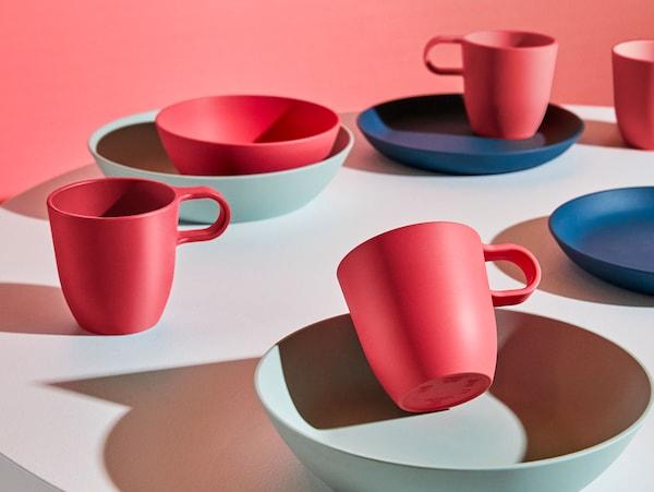 圆桌上摆满了红色、深蓝色和浅绿色的杯碟碗盘,均来自选用PLA塑料的 TALRIKA 塔利卡 系列。