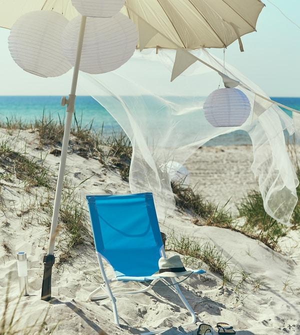 在白色大伞和太阳能吊灯下,摆放着一把蓝色沙滩椅。