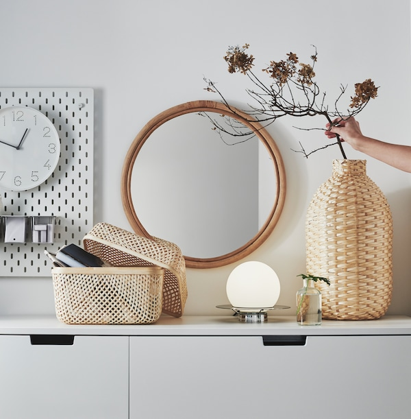 在白色的柜子上,有一个KAFFEBÖNA 卡布纳 装饰花瓶和一个SMARRA 斯马拉 储物盒,均为竹制。