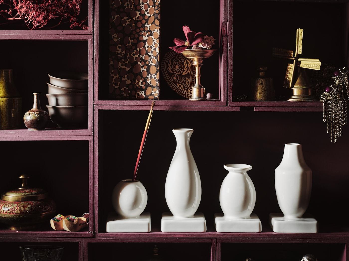 在摆放装饰品的储物柜上,有一套形状和大小各不相同的四件式KRINGGÅ 克里加 花瓶,白釉石瓷制成。