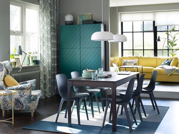 在餐厅内,EKEDALEN 伊克多兰 深棕色伸缩型餐桌旁摆放六把 ODGER 奥德格 蓝色椅子。背景中还可以看见一张黄色沙发。
