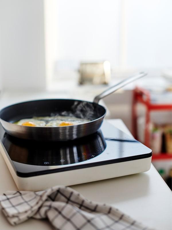 在厨房工作台上,TILLREDA 提瑞达 便携电磁炉的平底锅正煎着两个鸡蛋,旁边有一条厨房毛巾。