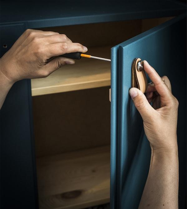 在定制涂漆的 IVAR 伊娃 储物柜上安装皮革把手。