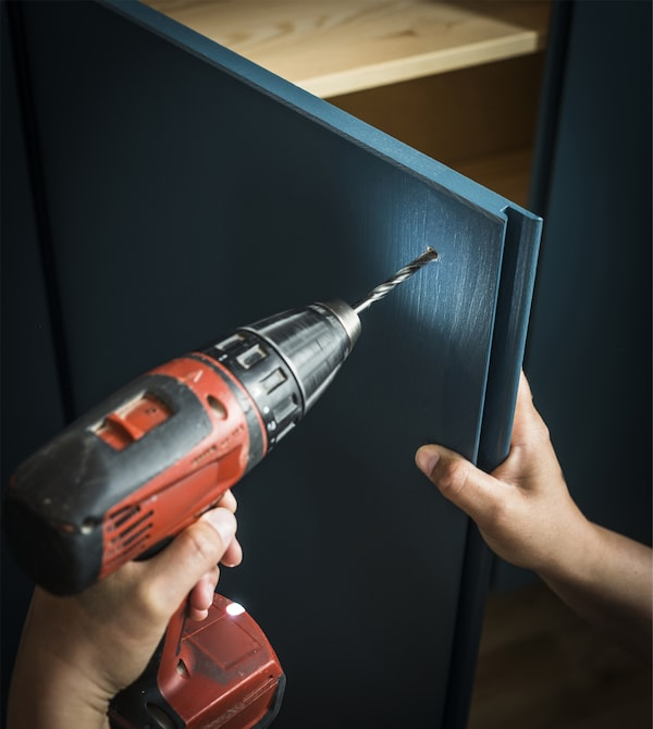 在定制涂漆的 IVAR 伊娃 储物柜上钻洞,安装门把手。