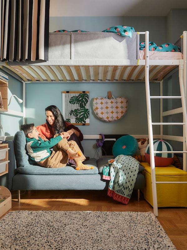 在儿童房里,一个女人和一个男孩正坐在白色VITVAL 维特瓦尔 高架床下层一个舒适的角落里。