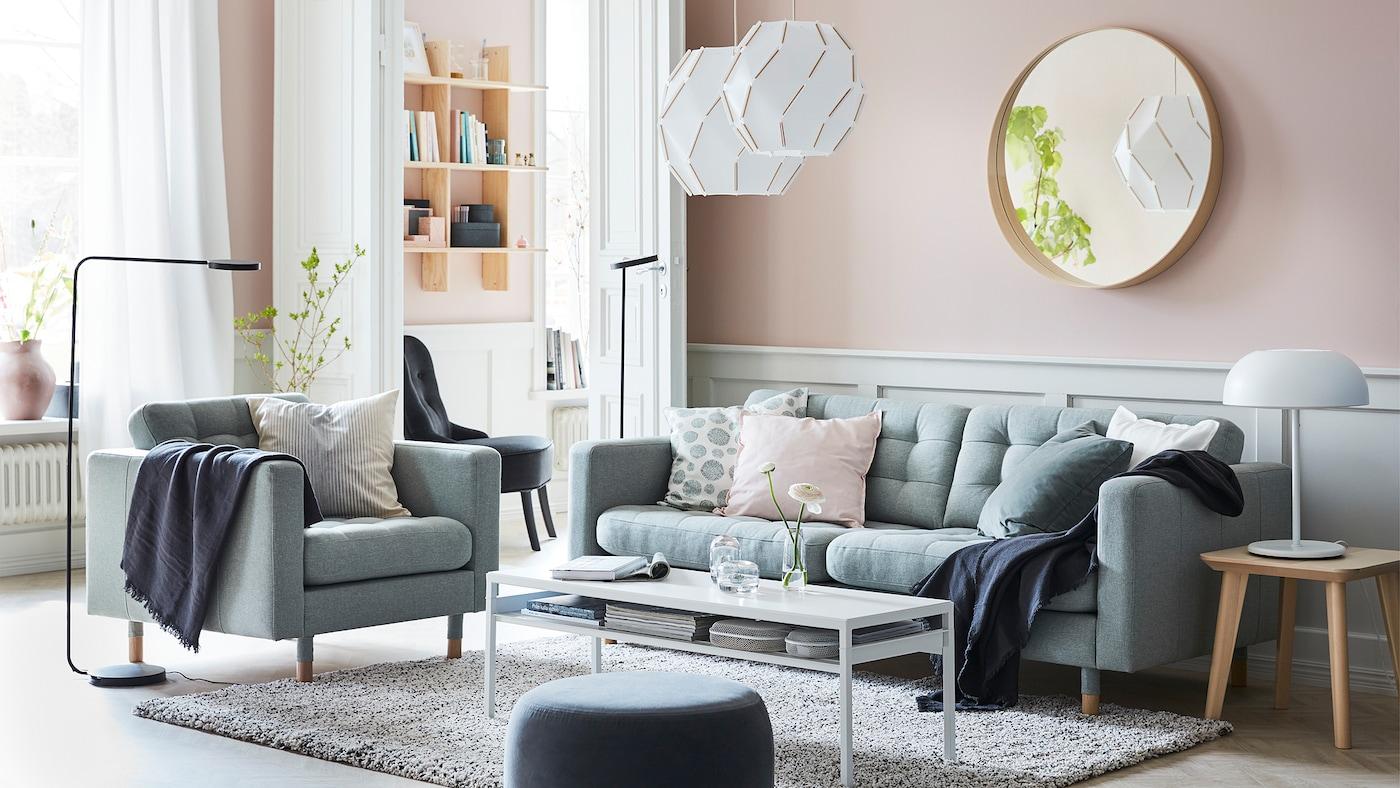 在粉色墙壁的客厅里,有浅绿色的LANDSKRONA 兰德克纳 沙发、SJÖPENNA 斯宾纳 吊灯和黑色的YPPERLIG 伊波利 落地灯。