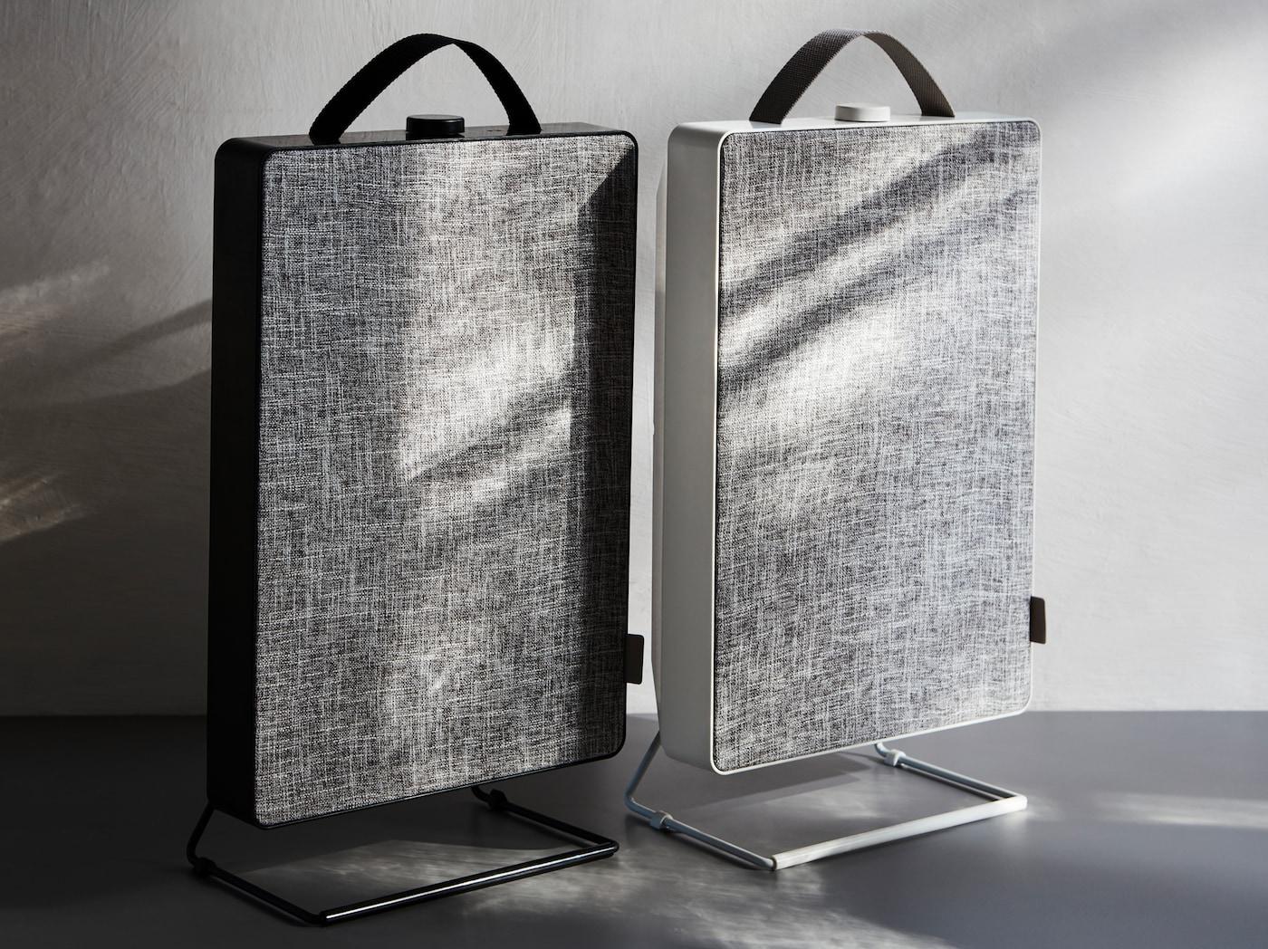 在灰色调的简约环境中,两台黑色和白色FÖRNUFTIG 费努福提 空气净化器并列排放着,正面均为灰色。
