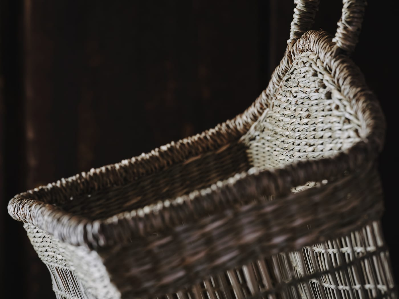在昏暗的环境中,有一个天然水草编织成的LUSTIGKURRE 卢迪古里 篮子,配有一个把手。