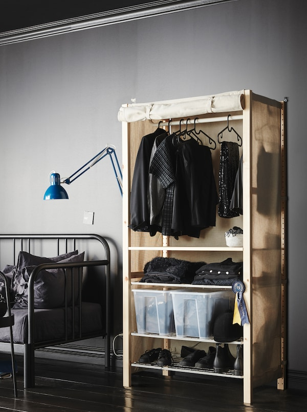 在简约的灰色房间中,添加布料外罩的IVAR 伊娃 搁架单元变成衣柜,装满各种衣服。