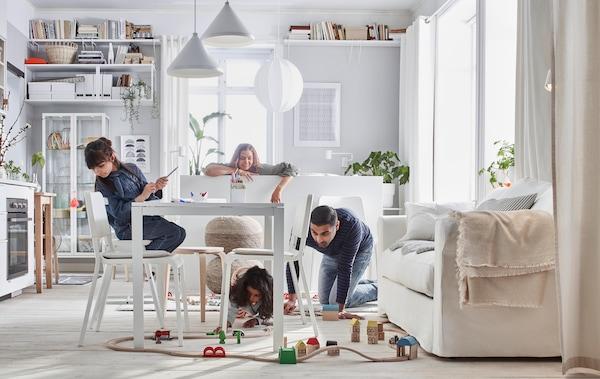 在紧凑的家里,一家人正在玩LILLABO 利乐宝 玩具火车。房间里有一张床、沙发、桌子、小厨房和储物单元。