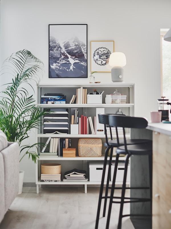 在开敞式格局的家居一角,有一张厨房多用桌,一张客厅沙发,还有一个摆满物品的BEKANT 贝肯特 搁架单元。