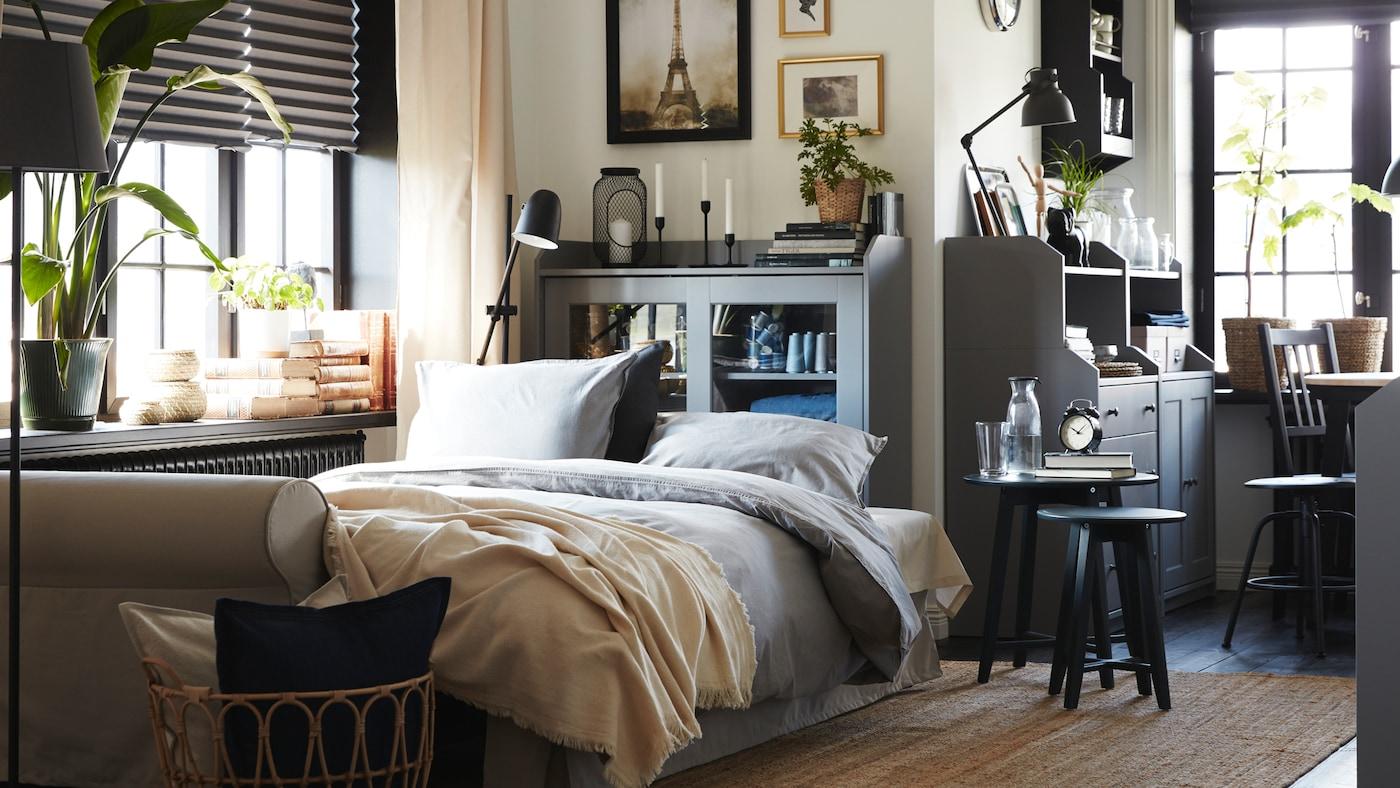 在客厅里有一张浅米色的沙发床,一张黄麻地毯、一张藤/竹椅子,以及两个灰色的储物柜和一个灰色的抽屉柜。