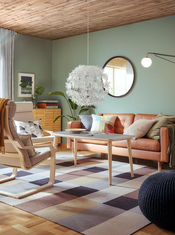 在客厅里,有一张沙发、沙发桌和两张浅褐色和白色的POÄNG 波昂 扶手椅,框架由浅色曲木制成。