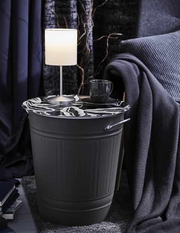 在 KNODD 克诺德 垃圾桶上摆放装饰性托盘,把它变成了一张边桌,上面有一盏灯和一杯咖啡。