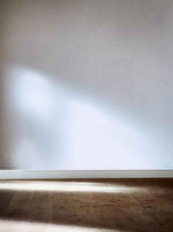 在空房间的一角,有一面白色裸墙,地板为天然原木。阳光从一侧照射进来。
