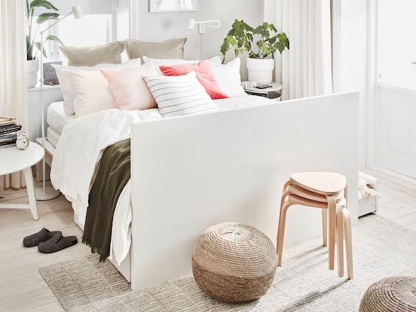 在明亮的房间里,白色的MALM 马尔姆 双人床,摆放着多个枕头和靠垫,配有高高的床尾板。