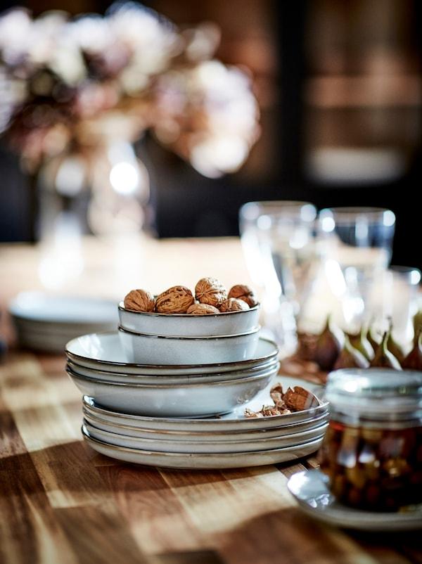 在木制桌面上,摆放着一堆GLADELIG 格拉德里 碗碟,旁边还有一些罐子、玻璃杯和小吃。