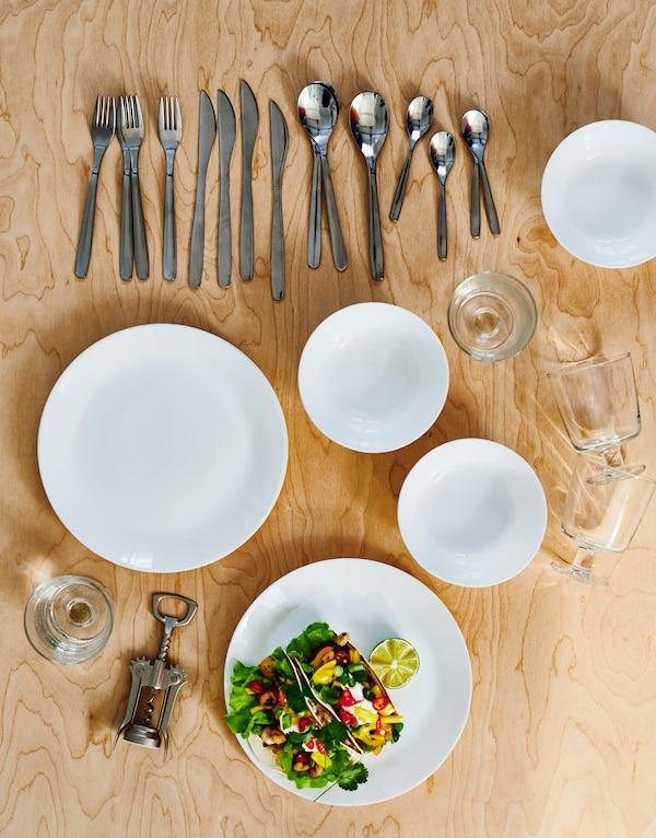 在浅色木质桌面上摆放着各种餐具:白色的OFTAST 奥夫塔 碟和碗、MOPSIG 默普斯格 刀叉、酒杯和开瓶器。
