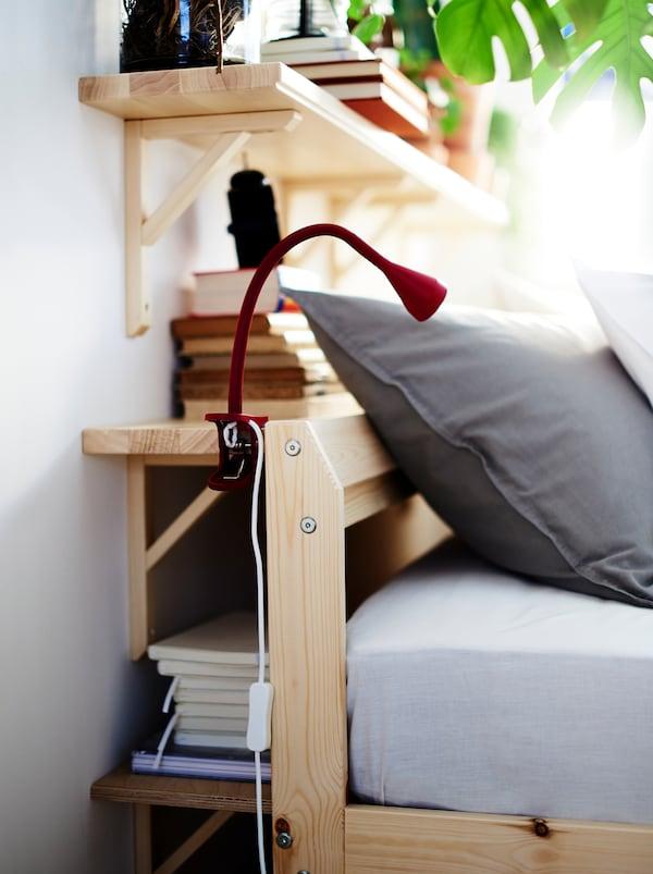 在墙壁和床头之间的空间安装了墙搁架,既是储物柜,也是床头桌。