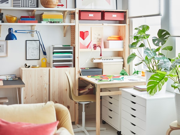 在全墙宽的IVAR 伊娃 储物单元一端是由折叠桌形成的办公区,上面铺满了彩色纸。