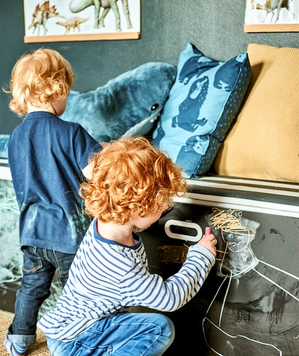 在涂黑板漆的柜门上,两个孩子正使用粉笔在抽屉上画画。