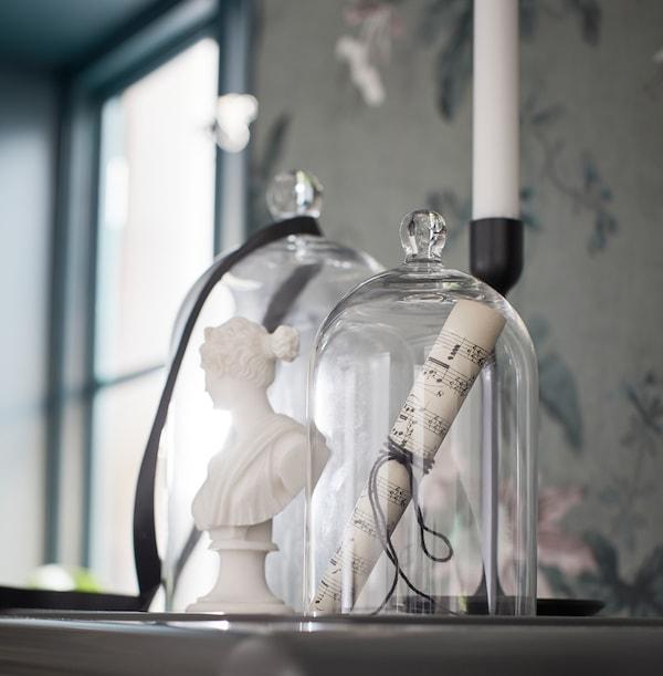 在一个柜子顶部,有一个烛台和两个大小不同的MORGONTIDIG 穆隆提迪 玻璃圆罩,里面装有一些音乐相关的装饰品。