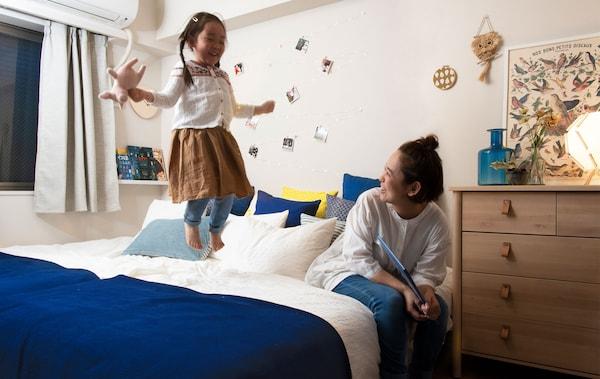 在一间白色卧室里,一位女士坐在大床上,孩子站在床上,房间里还有一个壁装书架。