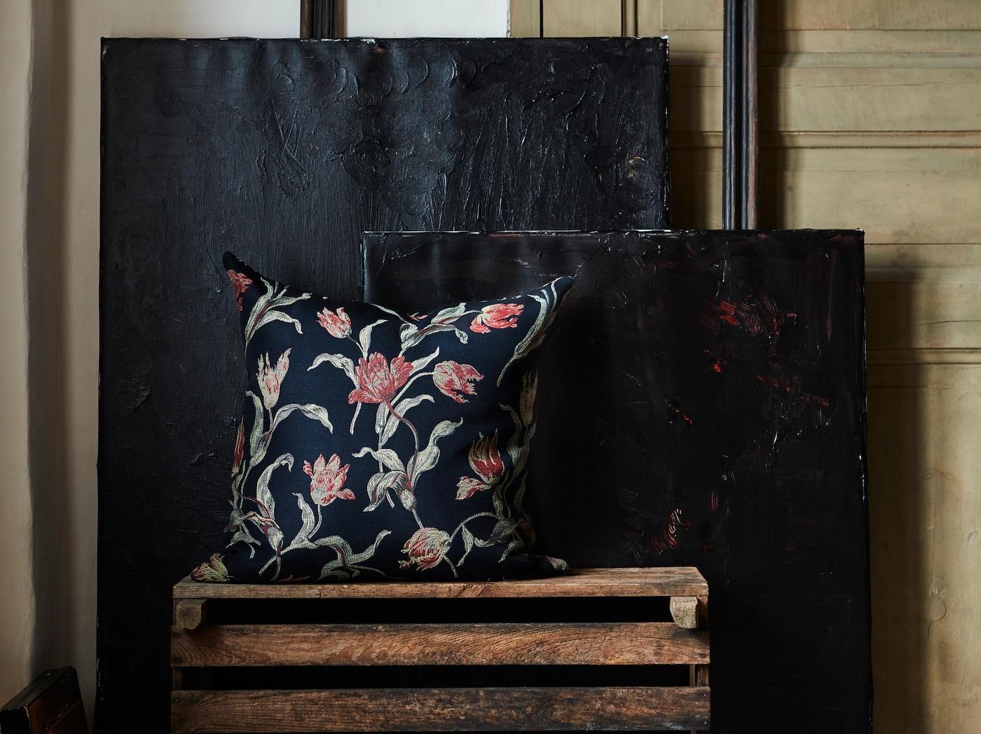 在一间昏暗的房间里,一个木板箱上摆放着手工刺绣的郁金香图案ÅLANDSROT 土木香 靠垫,后面是深蓝色的背景。