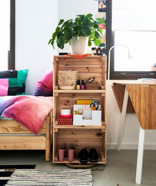 在一张床和一个小型餐桌中间,摆放着由三个木箱侧面堆叠而成的书架,书架里摆有少许书。
