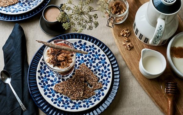 早餐桌上铺着亚麻布,摆放着蓝色图案盘子和装有格拉诺拉麦片的杯子,咖啡餐具则放置在砧板上。