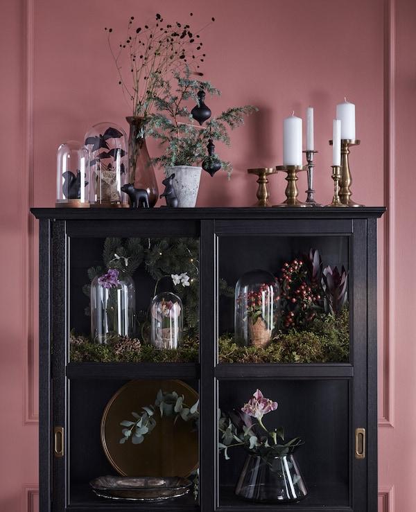 展示柜摆满了绿植、花朵和玻璃罩,装饰效果显著。