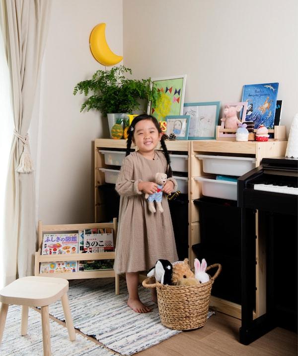 照片中,Mieko的女儿站在客厅内的玩具储物单元旁。