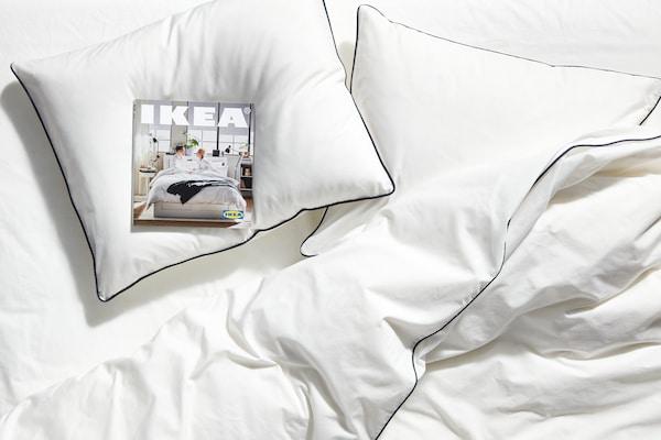 罩有白色床罩的床上摆放着白色的枕头,其中一个枕头上放着一本2020年宜家《家居指南》。