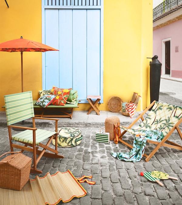 折叠摇椅和躺椅带有绿色图案和印花,摆放在鹅卵石地面上。