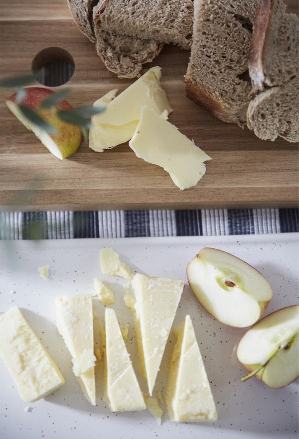 砧板上摆放着切成楔形的几块奶酪、苹果和面包。