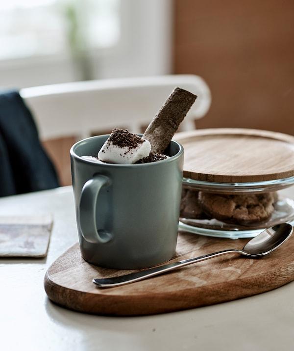 砧板上的灰蓝色马克杯里盛有棉花软糖热巧克力,旁边带竹材盖子的玻璃罐里装着饼干。