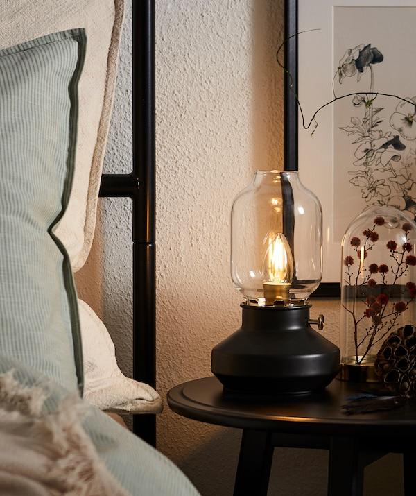 枕头立在带高床头板的床的边沿,圆形床边桌上放着煤油灯造型的LED灯具。