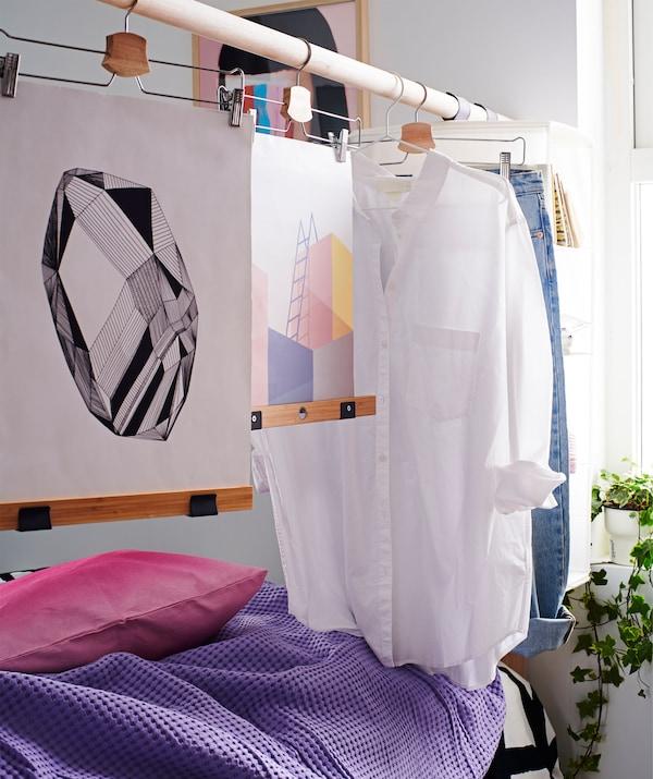 主要由高架杆组成的床头板充当着房间隔板,衣服和艺术品挂在挂衣架上。