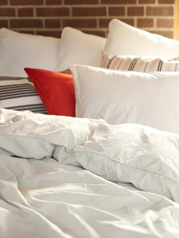 砖墙边靠着一张床,床上放着未整齐铺平的米色条纹BERGPALM 贝利帕姆 被子和枕套。