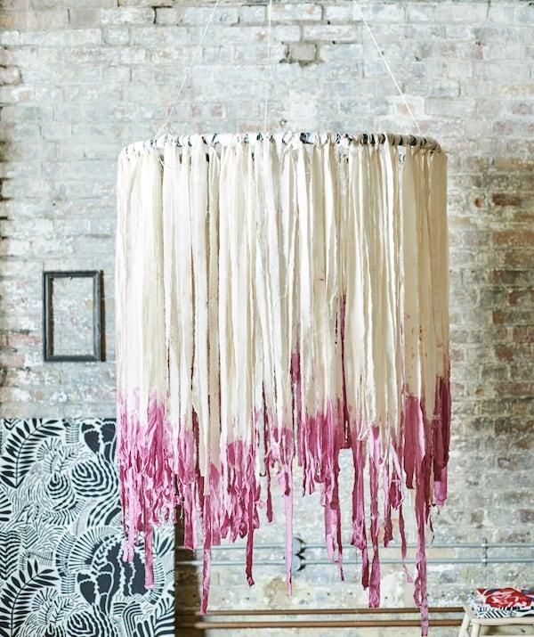 砖墙边悬挂着波西米亚风格转转乐。圆环上饰有流苏状的白色布条,两端染成了粉红色。