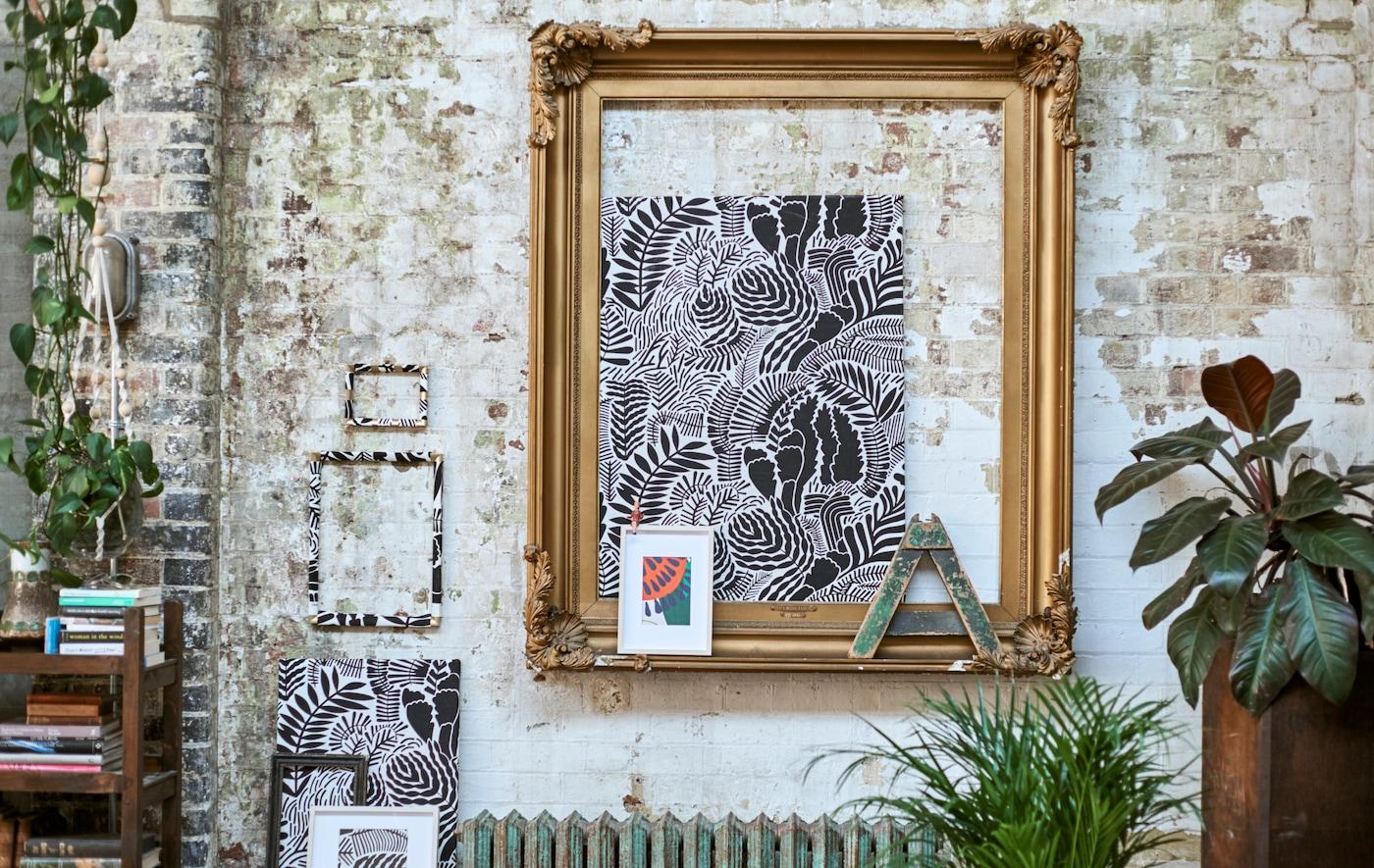砖墙上展示着饰有图案的装裱布料,如同美丽的画廊一般,此外还有大号的金色画框、垂吊植物和矮书柜。